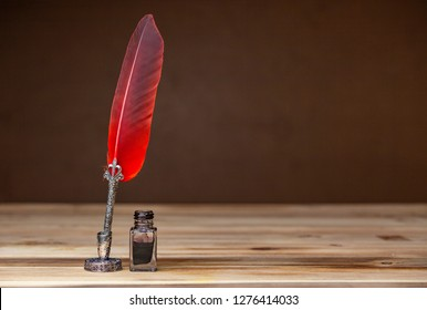 A red and silver quill pen, stand and an ink bottle on a wooden table.