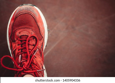 red single sneaker without a pair of shabby from a long walk or run on a brown worn background
