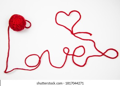 Red skein of thread against white background. Red ball of wool with red thread writes a word LOVE isolated on white. Heart and word Love written by red thread.