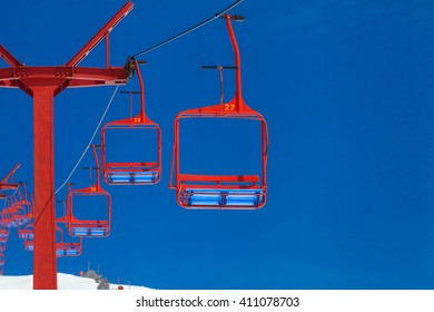 red ski lift, dark blue sky, snow and no people on it and at the mountain