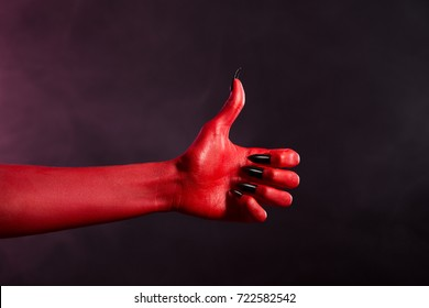 Red skin devil hand with black nails showing thumbs up, Halloween theme