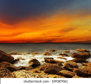 Red sky over a rocky seashore. Sunset landscape.