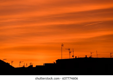Red sky sunset with clouds, roofs, antennas