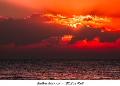 Red sky tropical sunset. Beautiful cloudscape with blood orange light from sun behind cloud. Lens flare stars add to the spiritual nature of the serene image.