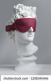 Red sleeping mask.  Gypsum statue of Apollo's head. Man. Statue. Plaster statue of Apollo's in red sleep mask.