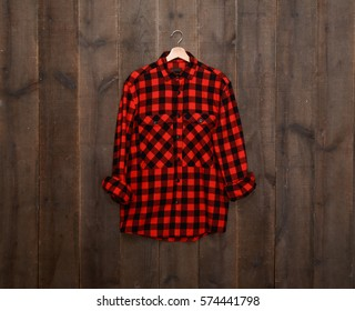 Red sleeved plaid cotton shirts on hanger –wooden background