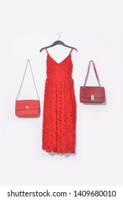 red sleeveless dress with red flower pattern and red leather handbag on hanging