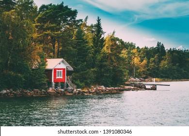 Red Small Finnish Wooden Sauna Log Cabin On Island In Autumn Season.