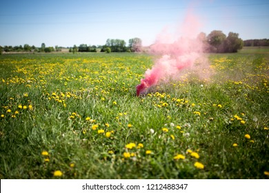 Red smoke on green graff field with heaven in background