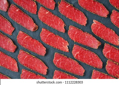 Red smoked meat slices with spices on a dark  blue background