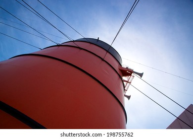 Red smokestack on cruise liner with lines and rigging leading up to it.