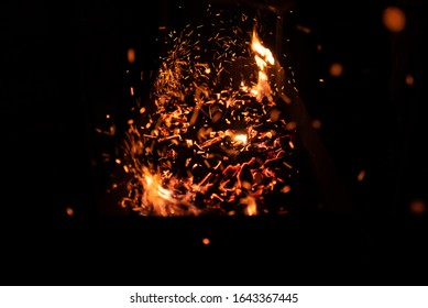 red smoldering embers in a barbecue with flying icters on a black background