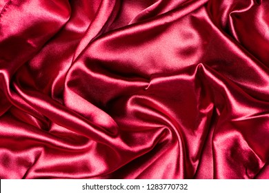 Red smooth elegant satin texture, can be used as abstract design background for wedding, valentine or advertising design, fabric pattern