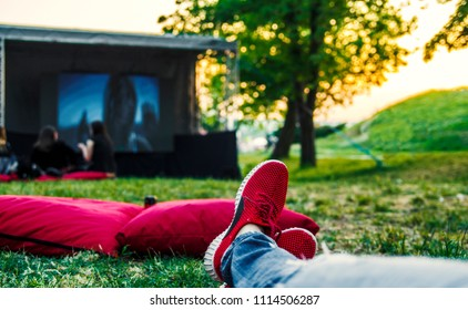 Red snickers shoes on ground and big movie screen in open cinema in green public park.Enjoying and relaxing on summer weekend.