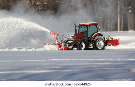 Red snow blower clears snow-covered streets in Montreal, Canada