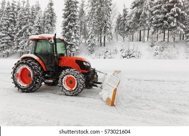 Red snowblower grader clears snow covered ski resort road in mountains or city street. Winter snowflake snowfall weather. Horizontal, copy space.