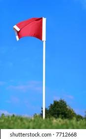 Red soccer corner flag against blue sky on green field