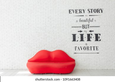 Red sofa lips shape on white brick wall background. Minimalism concept