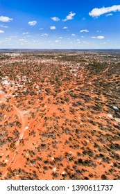 Red soils of Australian Outback around Lightning Ridge town - the centre of opal mining and black opals mines in Australia. Elevated aerial vertical panorama over grounds and opal shafts.