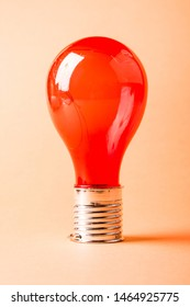 Red solar power light bulb on abstract orange background. Ecofriendly solutions concept.