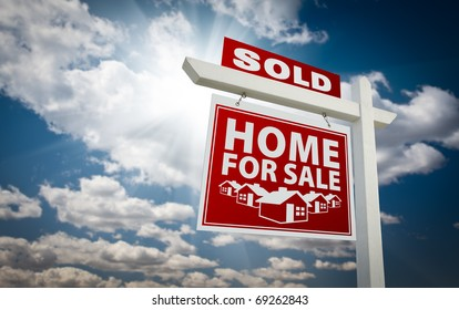 Red Sold Home For Sale Real Estate Sign Over Beautiful Clouds and Blue Sky.