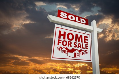 Red Sold Home For Sale Real Estate Sign Over Beautiful Clouds and Sunset Sky.