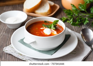 red soup with sour cream and greens