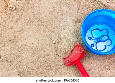 Red spade and blue bucket in the children's sandbox. View from above.