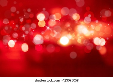 Red sparkles glitter and rays lights bokeh abstract holiday background/texture.