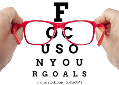 Red spectacles focusing on text focus on your goals arranged as eye chart test