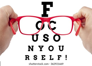 Red spectacles focusing on text focus on yourself arranged as eye chart test