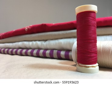 Red spool of thread in front of stacked folded fabric in stripes and solids
