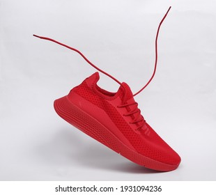 Red sports shoe with flying laces on white background
