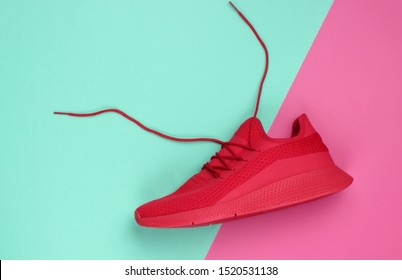 Red sports sneaker with untied laces on a blue-pink paper background. Creative sport still life, minimalism. Top view