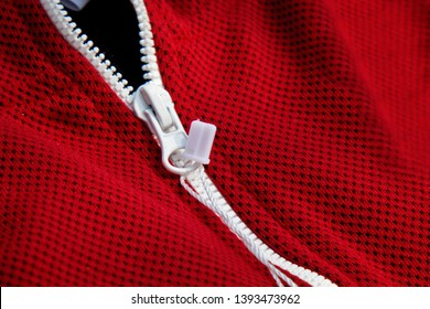 red sportswear closeup top view. white zip line. breathable knitwear. clothing details macro.