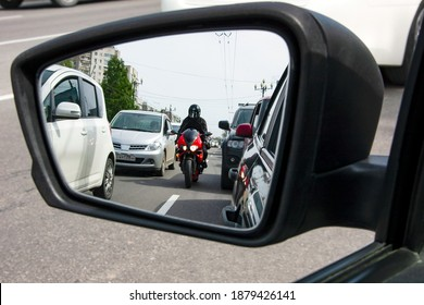 A red, sporty, motorcycle moves between the lane, dangerously close to cars.