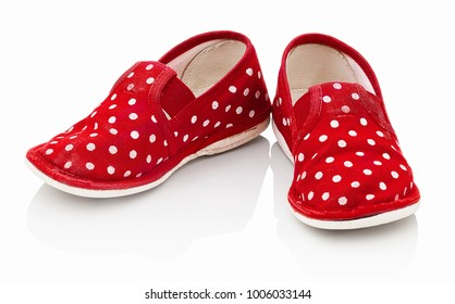 Children´s red spotted slippers isolated on the white background. Kid´s red slippers with white spots. Comfortable slippers isolated on the white background with shadow reflection.