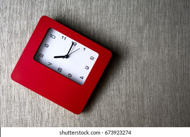 The red square alarm clock on fabric velvet sofa with morning light