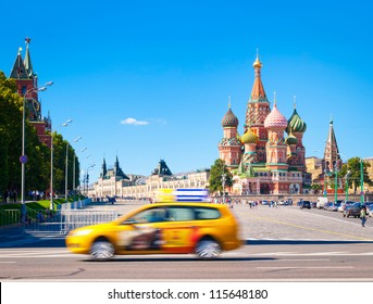 Red Square with the Kremlin and St. Basil Cathedral at nice summer day with clear blue sky in background and yellow taxi car in foreground. Most popular tourist destination in Moscow, Russia.