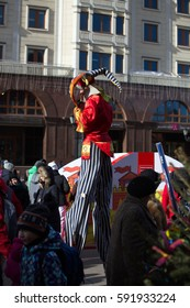 Red Square, Moscow -- February 25, 2017: Seeing Pancake, costume show with participation of the people. Skomaroh, parsley on stilts in a red shirt talking on a city.