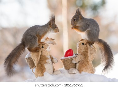 red squirrels are standing on a bunny with red egg