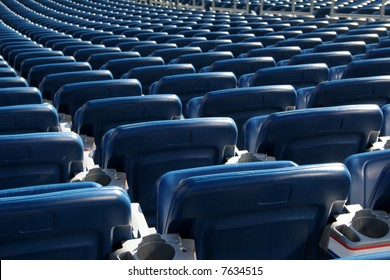 Red staduim seats cast in bright sunshine and shot from behind.