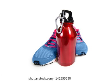Red stainless steel water bottle with running shoes over white. Exercise and hydration concept.