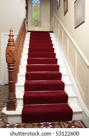 A red stair carpet with traditional brass rods