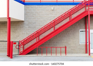 Red staircase against stone textured wall