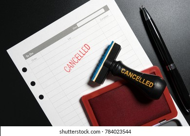 Red stamp with text cancelled on business to do list table on black background. Reminder to cancel business appointment. Business cancelled rejected abort declined cancellation denied concept.