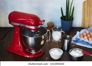 red standing mixer kitchen aid on wooden table with cream cheese eggs glass flower