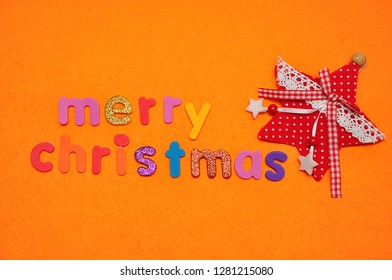 A red star and Merry Christmas on an orange background