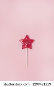 Red Star Shaped Lollipop on Light Pink Background Homemade Fruit Lollipop Candy Background Flat Lay Top View Vertical
