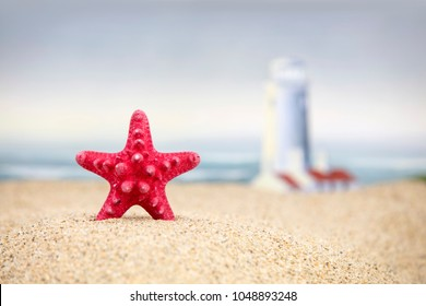 A red starfish with a lighthouse in the background at the beach.